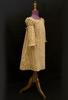 Ca 1820 roller printed cotton child's Regency style dress with double sleeves and ribbon ties at back high waist. This originated in a New England family.