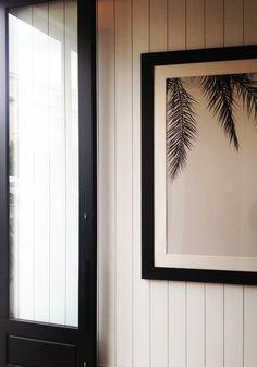 black metal door white wood wall panelling
