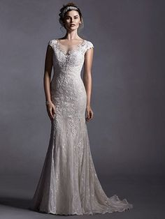 Sottero and Midgley - QUINLYNN, Glamorous, glimmering  lace appliqués adorn tulle in this sheath dress with illusion neckline and plunging illusion back. Complete dainty  lace cap-sleeves. Finished with covered button over zipper closure.