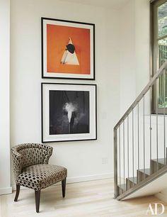 A minimalist stairway landing featuring artwork by Madeleine Farley | archdigest.com
