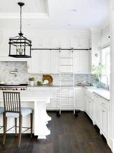 Iron and glass lanterns hang from a shiplap tray ceiling over a white center island seating wood spindle counter stools with blue seat cushions at a white quartz countertop.