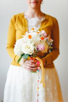 Fabulous wedding bridal bouquet. Daffodils with orange centers are the real pop, but the other flowers are lovely too (roses, hydrangea...). And how about that vintage button dangle?