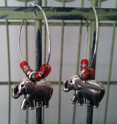"Crimson Tide Earrings Silver-tone hoops with red and gray seed beads and a silver-tone elephant charm. Show your spirit on Game Day! Roll Tide! Hoop is 1"". Elephant is 0.75"" X 0.5"""