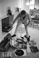 Steve McQueen at his Palm Springs bungalow puts on a records with LPs by Miles Davis. Sonny Rollins, and Frank Sinatra scattered at his feet.