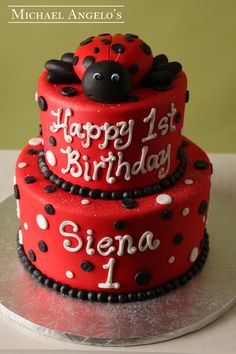 Red Polka Dot Lady #11Milestones  This two tier cake is iced in smooth red fondant and features black and white polka dots. The borders are piped in black buttercream and the birthday message is written in white buttercream. A gum paste lady bug tops the cake for an extra special touch.
