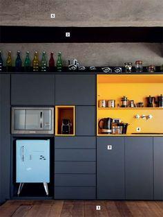 5 Inspirações de Cozinhas Escuras - Se você, como eu, já é maníaco por cores escuras, vai entender porquê eu amo tanto essa ideia. Misturar o chão de madeira, com um armário marinho e, de repente, colocar um amarelão para a área da pia dá toda a cor que essa cozinha precisa. Tanta cor que dá pra esquecer daquela ideia de que ambientes escuros são pesados, não acha?