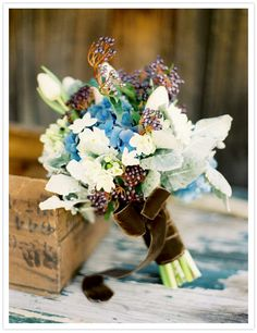 Lovely bouquet of simple tulips and paperwhites, textured with berries and a big velvet ribbon.