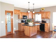 This kitchen is by Leewood Homes at 1150 N. Countrywalk in our community,Rockwood Falls, in Rose Hill, KS. It features hardwood flooring, walk-in pantry, and an island with granite counters.