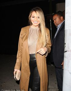 Glowing: The beauty produced a trademark pearly white smile for the cameras as she exited the bar dressed in a billowing tan overcoat, a golden semi-sheer top and wet-look leggings
