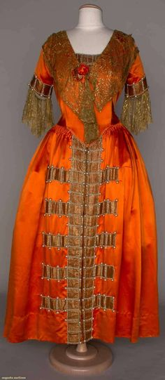"Burnt orange silk satin; bands of lame trimmed w/pearls on CF skirt, sleeve ends, and modesty panel; bodice trimmed w/gold lace flounces. Label: ""Lanvin Paris."""