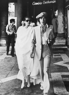 Mick and Bianca.    Designers like Tom Ford (who favors strong lapels and chunky neckwear) have famously cited Tommy Nutter as an influence. Bianca on Mick Jagger's arm as he struts in his Tommy Nutter duds– from the book Day of the Peacock by Geoffrey Aquilina Ross that is an incredible visual chronicle of the flashy and flamboyant menswear style from 1963-1973.