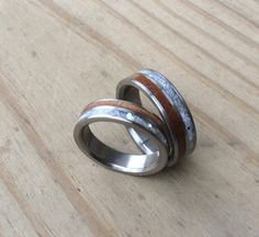These gorgeous custom made wedding rings are two of our hand milled and sized titanium rings, each with two inlays. One is 50,000+ year old ancient