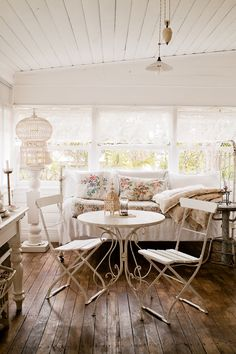 Pretty boho shabby chic entertaining area on the porch. Gorgeous timber floor boards, vintage decor and white feminine textiles.