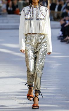 This metallic **Isabel Marant** trouser is rendered in silk and features a high rise with a drawstring waistband, a harem pant style with large slip pockets, and a slim leg silhouette