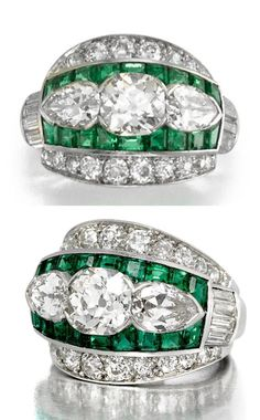 AN ART DECO DIAMOND AND EMERALD RING, MARCUS & CO., CIRCA 1935. Centring an old mine-cut diamond, weighing approximately 1.00 carat, flanked by two old pear-shaped diamonds within an emerald surround, to baguette-cut diamond shoulders within a border of old single-cut and old European-cut diamonds; signed Marcus; mounted in platinum. #Marcus #ArtDeco #ring