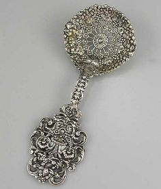 A large Tiffany sterling cast bon bon serving spoon with a light gold wash. Intricate cast detail with a cornucopia and swags on the handle. Fully marked including the T mark (1891-1902
