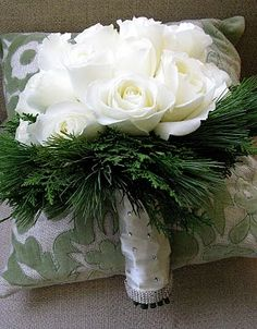 White rose, evergreen, and pine sprig bridal bouquet. Perfect for a winter holiday wedding.