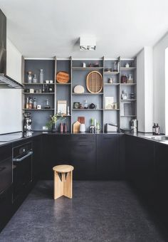 Stylish kitchen with a grey backwall, black cabinets and lots of open storage solutions.