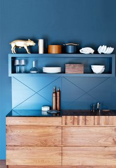 Beautiful natural wood base cabinets with bold painted wall cabinets.