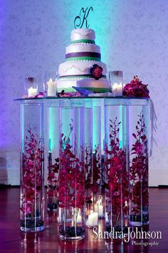 What a unique idea to use tall glass vases and a piece of glass for the wedding cake ... I can see this with fish in the vases or colored marbles