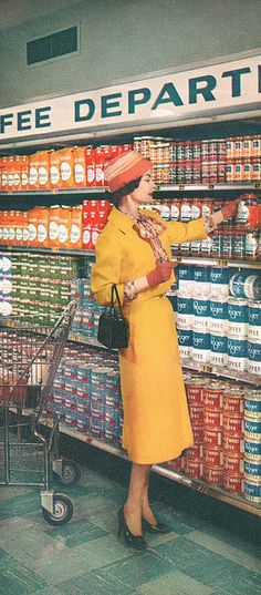A stylishly attired woman shops for coffee at a Kroger supermarket, 1957. #vintage #1950s #supermarket