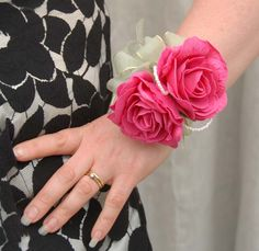 A stunning artificial Wedding wrist corsage, with two cerise  Isabel roses, with loops of small pearls and a small ivy leaf   underneath.  Lovely apple green  sheer organza bow and matching apple  green sheer ribbon to tie to the wrist.     Measurements  Width:- 4.5 inches  Length:- 4  inches    Wrist corsage from Sarah's Flowers