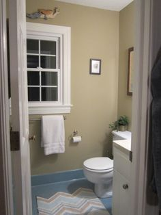 Master Bath- AFTER:  To tone down the SMURF BLUE tile, I chose Benjamin Moore Bennington Gray HC-82 and a rug with both blue and camel color in a modern chevron pattern for a crisp updated look.  The wall color minimized the contrast, and made the dated blue tile look FRESH