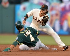 Oakland Athletics' Coco Crisp (4), left, is tagged out by San Francisco Giants' Brandon Crawford (35) as he tries to steal second base in the third inning of their baseball game held at AT&T Park in San Francisco, Calif., on Wednesday, July 9, 2014. (Doug Duran/Bay Area News Group)