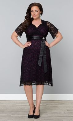 Channel your vintage Hollywood starlet in Kiyonna's plus size Retro Glam Lace Dress.  The purple lining shines through black lace in an A-line silhouette.  A removable satin sash and brooch cinch the waist for an even more flattering look. Shop made in the USA styles at www.kiyonna.com.  #Kiyonna #lacedress #lbd