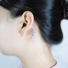 Tiny blue flower tattoo behind the left ear. Tattoo artist: Sol...