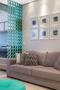Nesta sala, projetada por Marcy Ricciardi Arquitetura, o elemento vazado produzido em madeira divide os ambientes sem carregá-los.