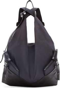 Canvas and leather backpack in black. Adjustable carry handle at top of bag. Criss-crossing shoulder straps. Zip pockets at face with adjustable cinch-straps. Embossed logo at side. Two-way zip closure to main compartment at back panel. Tablet compartment and zip pocket at main compartment interior. Textile lining. Tonal stitching. Approx. 16