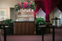 A brown tufted bar with dark wood cocktail tables and bright tropical colored florals continued the theme (Venue: @bevhillshotel   Planner: @internationaleventco @margot_iec   Design Décor and Florist: @theemptyvase @emptyvaseyvonne   Photographer: @jessicaclaire   Videographer: @cloudlessweddings   Lighting: @images_lighting   Décor: @revelryeventdesign @revelrymatias   Band: @liventgroup   Linens: @latavolalinen   Ceremony Chairs: @chiavarichairrentals   Reception Chairs and Chargers…