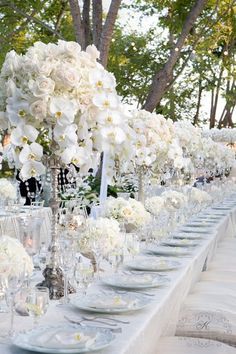 White hydrangea, white phalaeonpsis orchids and white roses on a silver candlestick riser
