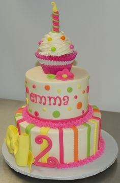 """An over-the-top cake I love!  If only I could do fondant frosting.  It's a 6"""" strawberry cake with an 8"""" chocolate cake. The jumbo cupcake on top is strawberry cake and was especially for the birthday girl. The entire cake was frosted in vanilla buttercream. Decorations are fondant and gumpaste."""