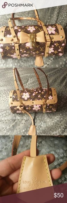 Louis Voutton Cherry Blossom Purse Replica Well made replica! Studded details: missing 1 stud at the top left corner. Surface scratches on goldtone hardware and decorative lock. Interior in good condition with normal signs of wear.  Classic rounded shape with two straps. The body is constructed from dark brown canvas and splashed with vibrant Japanese cherry blossoms with happy expressions. Exterior in good condition with a tiny spot where peeling started to occur. Accessories