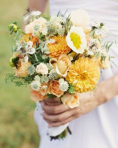 Peach dahlias and roses mixed with poppies, scabiosa, nigella, astrantia, and peppergrass in a bouquet made by Angela Ingram.