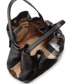Burberry grained leather and signature check canvas tote bag. Shoulder straps with rings. Snap-down gusset sides. Four exterior zips expand body. Snap top closure. Check canvas lining; one zip pocket.