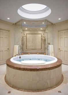 A circular master bathroom with a skylight over the free standing tub offers a separation between his-and-her vanities.
