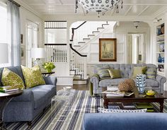 The living room evokes a traditional mid-20th-century American sensibility, but with a modern twist. Watson's senior designer Wendy Monette mixed colors, patterns, and styles that lend a clean, graphic edge to the room, like the sofa's superscaled houndstooth with the rug's green and navy stripes. Lucite tables with an antique English country coffee table.