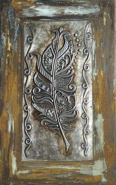 solo una pluma repujado en aluminio, con incrustaciones de piedras y pintado con patinas