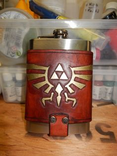 This is a stainless steel flask and a 5-6oz Leather flask holder, with a D ring for attaching to the belt. The flask holder is hand tooled and dyed using eco-flo leather dye and painted in a gold metallic paint. This comes with both the flask and belt clip carrier. The flask may not be