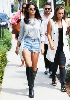 Selena Gomez wears a drapey gray t-shirt, cutoff shorts, knee-high leather boots, silver jewelry, and clear frame sunglasses