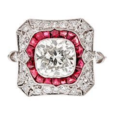 Cushion Cut Diamond Ring accented with tile set rubies and diamonds in a platinum filigree mounting. The center diamond weighs 2 carats and is framed with rubies followed by an outer frame of scattered diamonds. A beautiful handmade ring with unsurpassed detailing.