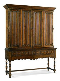 A handsome reproduction of a William and Mary cabinet with linen fold carvings on two bi-fold doors and two drawer fronts with antique brass hardware. This piece was designed to effectively house a flat screen TV and components. W64 D20 H84