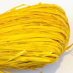 Fibres de raphia naturel en pelote de couleur jaune.
