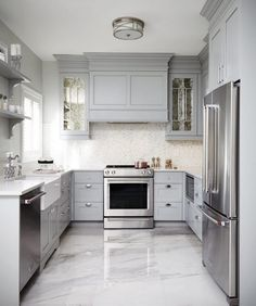 Modern Kitchen Design This gray u-shaped kitchen features a gray paneled hood flanked by antiqued mirrored kitchen cabinets and mounted against white and gray mosaic backsplash tiles over a stainless steel oven range. Grey Kitchen Cabinets, Kitchen Cabinet Design, Kitchen Tiles, Kitchen Interior, Kitchen Decor, Kitchen Grey, Kitchen Designs, White Cabinets, White Kitchen Floor Tiles