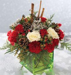 Roses, evergreens, pine cones, etc., in a square vase.