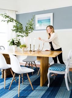 Bright dining space with indoor plant, modern chairs, and candlesticks