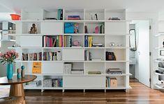 Para ligar os ambientes desde a cozinha até a sala de estar, a estante de laca branca, desenhada pelo escritório SAO Arquitetura, envolve o volume onde fica o lavabo. Com a cor em comum, os ambientes integrados ficaram uniformes